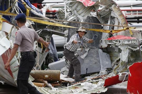 Các nhân viên từ Ủy ban An toàn Giao thông Quốc gia Indonesia đang kiểm tra phần đuôi máy bay hôm 12-1. Ảnh: Reuters
