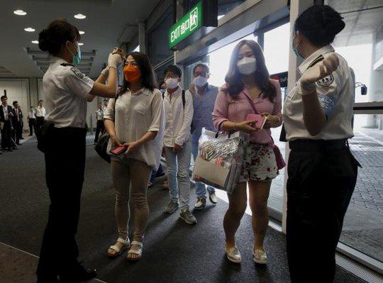 Du khách Hàn Quốc được kiểm tra thân nhiệt tại sân bay Hồng Kông. Ảnh: Reuters