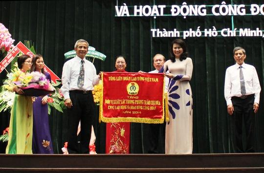 Ông Đặng Ngọc Tùng, Chủ tịch Tổng LĐLĐ Việt Nam, trao cờ thi đua xuất sắc của Tổng LĐLĐ Việt Nam cho tập thể thường trực LĐLĐ TP Ảnh: HOÀNG TRIỀU