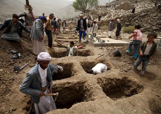 Người dân đào huyệt để chôn các nạn nhân của một vụ không kích tại làng Okash ở gần thủ đô Sanaa - Yemen hôm 4-4Ảnh: Reuters