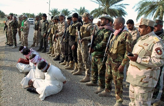 Chiến binh Shiite ở Iraq bắt được 4 nghi can IS bên ngoài nhà máy lọc dầu Beiji, Bắc Baghdad, hôm 28-5 Ảnh: AP