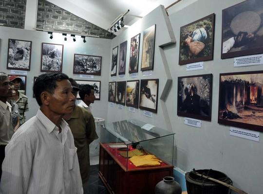 Ông Trần Nam xem lại những bức ảnh chụp cảnh người thân bị thảm sát được lưu giữ trong Khu Bảo tàng chứng tích Sơn Mỹ