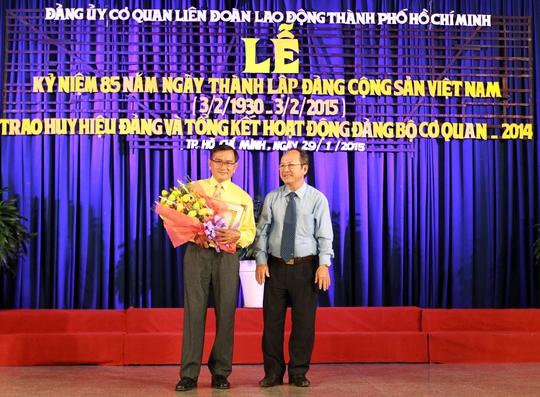 Ông Nguyễn Hoàng Năng (bìa phải), Bí thư Đảng ủy Khối Dân - Chính - Đảng, trao huy hiệu 30 năm tuổi Đảng cho đảng viên Võ Văn Tấn, Chi bộ Trường Trung cấp Công đoàn TP