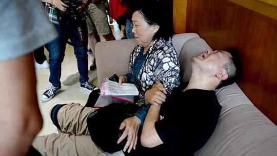 Thân nhân hành khách khóc ngất khi chưa biết tin tức. Ảnh: Reuters