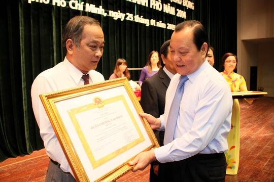 Ông Lê Thanh Hải, Úy viên Bộ Chính trị, Bí thư Thành ủy TP HCM, trao Huân chương Lao động hạng 3 cho ông Vương Phước Thiện, Trưởng Ban Tuyên giáo LĐLĐ TP Ảnh: HOÀNG TRIỀU