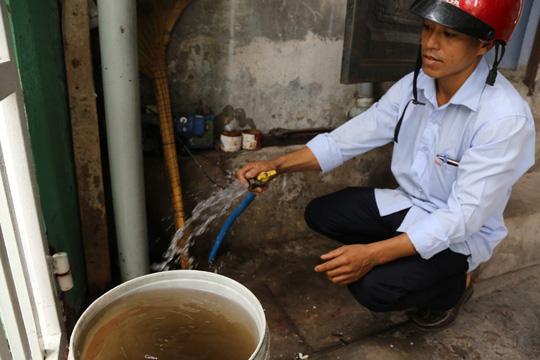 Nhân viên cấp nước đến nhà dân xả bỏ nước đen trước khi nước vào đồng hồ nước của dân