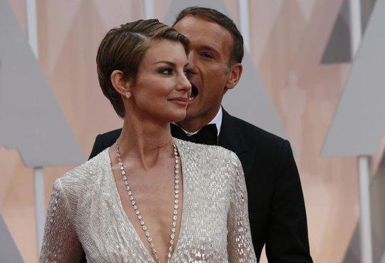 Tim McGraw làm hành động như ma cà rồng chuẩn bị cắn vợ là Faith Hill. Một kiểu tạo dáng lạ của họ trên thảm đỏ Oscar 2015