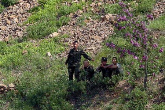 Binh sĩ Triều Tiên đứng trong tán cây ở TP Sinuiju. Ảnh: UPI