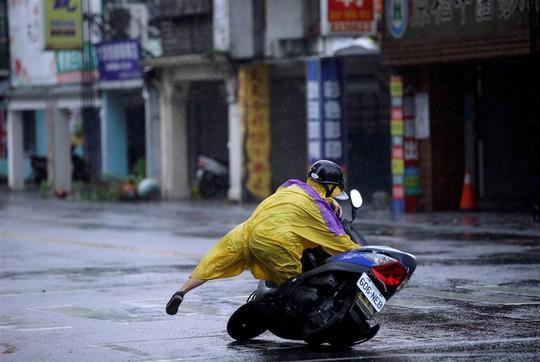 Một người đi xe gắn máy té ngã do đường trơn trượt. Ảnh: REUTERS