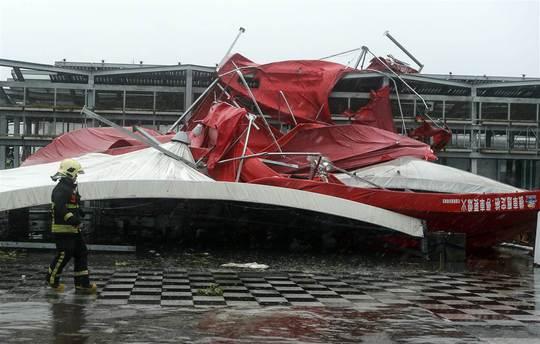 Lính cứu hỏa kiểm tra một chiếc lều bị gió mạnh phá hỏng. Ảnh: EPA