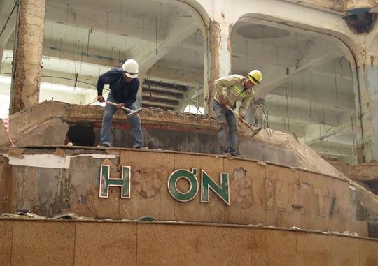 Hai công nhân tiến hành đập bỏ bảng hiệu Thương xá Tax trên nền gạch