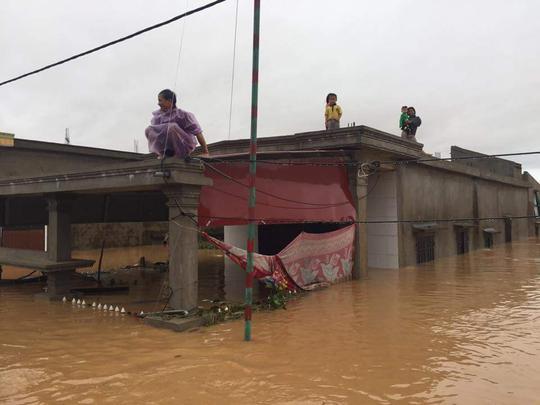 Lũ ngập người dân Cồn Sẽ (Quảng Lộc, thị xã Ba Đồn,Quảng Bình) lên nóc nhà tránh lũ (ảnh Minh Tuấn)