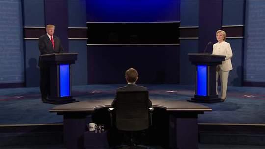Ông Trump (trái) và bà Clinton bước vào cuộc tranh luận cuối cùng tối 19-10 tại TP Las Vegas, bang Nevada. Dẫn dắt cuộc tranh luận là nhà báo Chris Wallace của đài Fox News. Ảnh: BBC