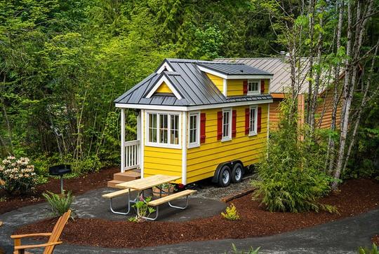 Một ngôi nhà nhỏ nhắn, xinh xắn được phủ lên mình lớp sơn màu vàng chanh bắt mắt, nổi bật giữa rừng cây xanh mướt