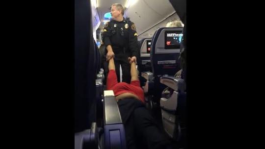 Hành khách bị kéo khỏi máy bay. Ảnh: YOUTUBE