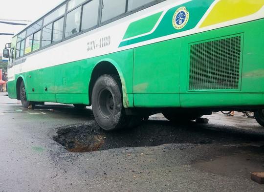 Bánh sau của chiếc xe buýt lơ lửng trên miệng hố