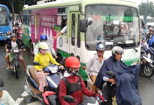 Một tiếp viên trên xe buýt phải nhô ra ngoài để xin đường lưu thông