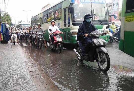 Nhiều người đi xe máy tránh vũng nước đọng trên mặt đường càng gây cảnh lộn xộn và kẹt xe