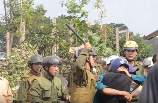 Lực lượng công an xã vây giật máy ảnh của phóng viên Đỗ Thanh Hải (áo khoác đen)