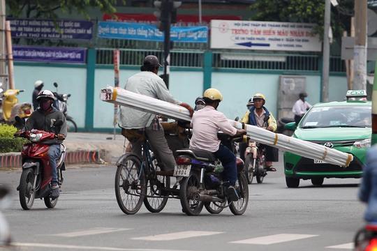 Nhiều xe xích lô không chạy nổi phải nhờ xe máy đẩy qua đường, ảnh chụp sáng 26-9