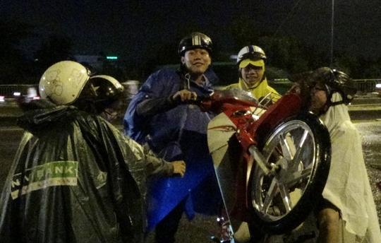 Một nhóm sinh viên đang cùng nhau nô lực làm khô xe, đạp xe nổ máy trở lại. Bạn Nguyễn Huy cho biết: Mình đang đi học về mà qua đoạn ngập, xe chết máy nên cả tiếng rồi vẫn chưa thể về nhà.