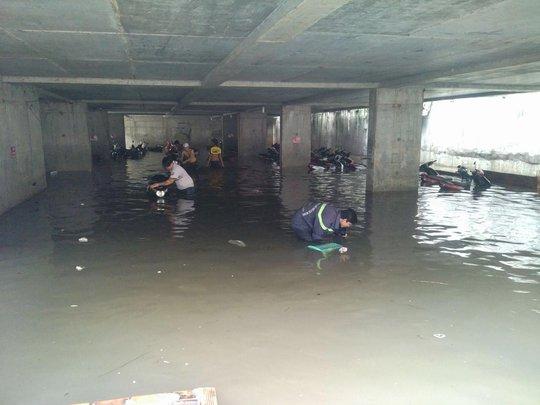 Nhân viên bãi giữ xe trên đường Nguyễn Siêu và lực lượng PCCC lấy xe từ tầng hầm sau cơn mưa tối 26-9