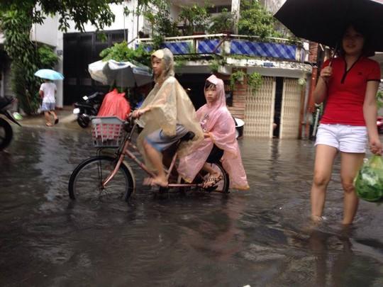 Các em học sinh phải đạp xe trong tình trạng ngập nước và ô nhiễm