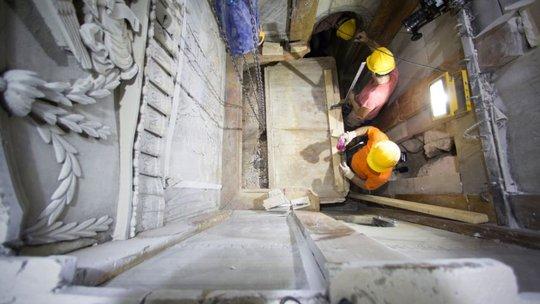 Các công nhân di dời phiến đá cẩm thạch che phủ ngôi mộ hôm 26-10. Ảnh: AP