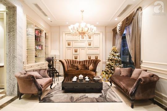 Phòng khách trang trí đơn giản với cây thông đính đầy quả châu sắc vàng kim và bạc nhã nhặn, sang trọng.