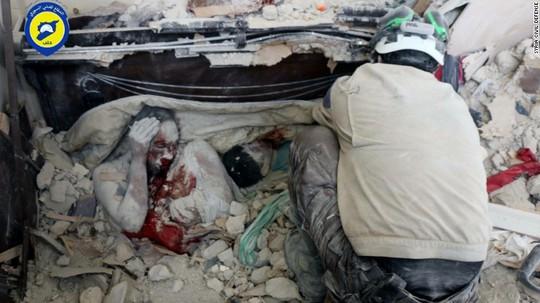 Thi thể hai nạn nhân trong đống đổ nát sau các cuộc không kích. Ảnh: CNN