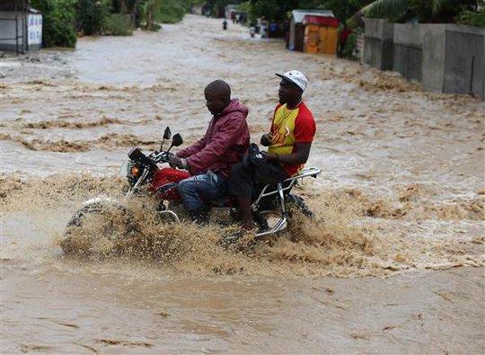 Người dân Haiti lái xe trong nước lũ. Ảnh: EPA