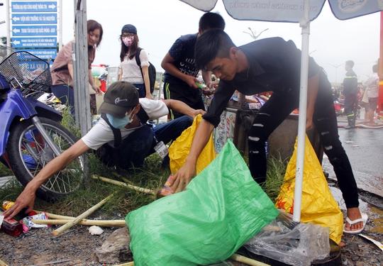 Các bạn sinh viên đang trên đường đi học về cũng nhiệt tình giúp thu gom hàng hóa vương vãi trên đường vào bao tải để tránh bị hư hỏng, thất thoát.