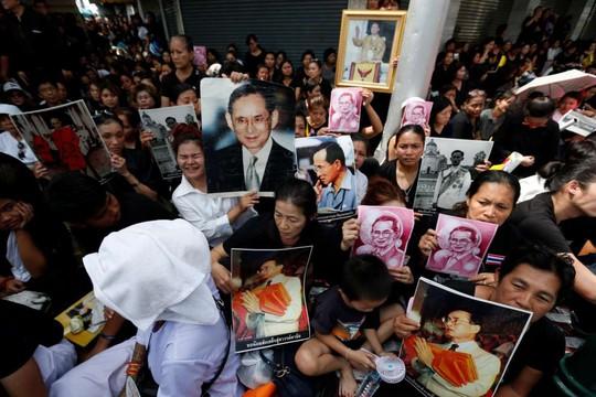 Nhiều người cầm hình Vua Bhumibol để tỏ lòng tôn kính. Ảnh: REUTERS