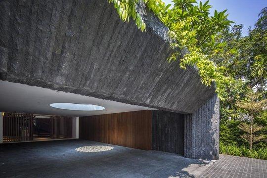 Tọa lạc trên mảnh đất hình chữ L, ngôi nhà có mặt tiền khá hẹp và đơn giản, che giấu không gian rộng rãi bên trong, góp phần bảo vệ sự riêng tư cho chủ nhân