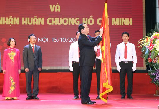 Chủ tịch nước Trần Đại Quang gắn Huân chương Hồ Chí Minh lên lá cờ truyền thống của Trường ĐH Bách khoa Hà Nội Ảnh: TTXVN