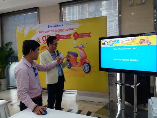 Chủ thẻ tín dụng quốc tế Sacombank (bên trái) tham gia quay số trúng thưởng