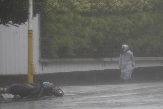 Người đi xe máy tại huyện Hoa Liên - Đài Loan khốn khổ vì bão hôm 27-9. Ảnh: REUTERS