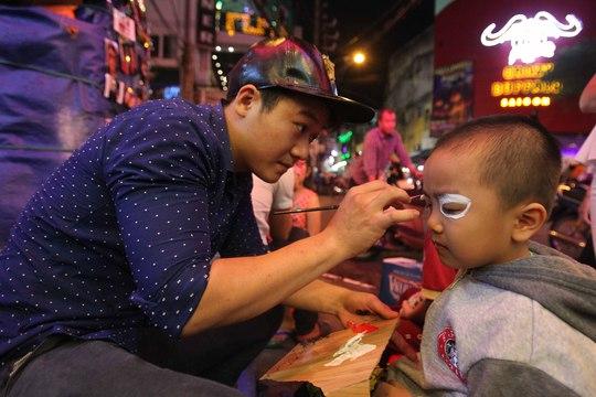 Anh Quang - một người chuyên vẽ mặt tại trung tâm thành phố cho biết một đêm như thế này anh có thể vẽ từ 30-40 mặt, giá 50.000 ngàn đồng/mặt.