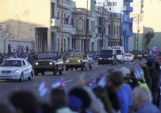 Người dân Cuba chụp hình và quay video đoàn xe. Ảnh: REUTERS