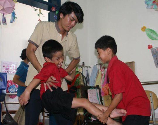 Trẻ khuyết tật giúp đỡ thầy cô chăm sóc bạn của mình