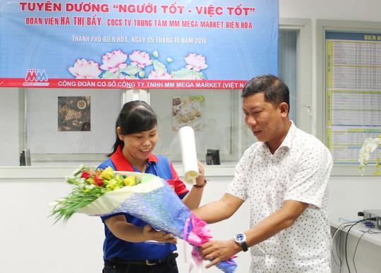 Ông Trần Đoàn Trung, Phó Chủ tịch LĐLĐ TP HCM, trao thư khen và tặng quà lưu niệm cho chị Hà Thị Bẩy