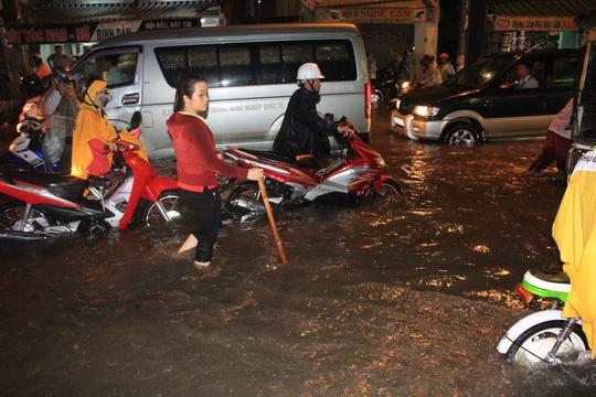 Một người phụ nữ phải chống gậy, mò mẫm lội trong dòng nước trên đường Nguyễn Xí (quận Bình Thạnh) vì sợ sụp phải hố sâu