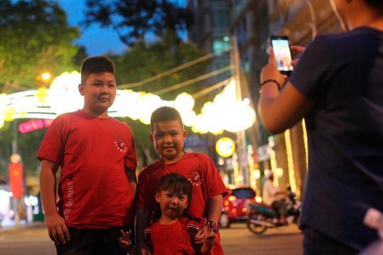 Một gia đình chụp ảnh trước cồng chào phía đường Đồng Khởi
