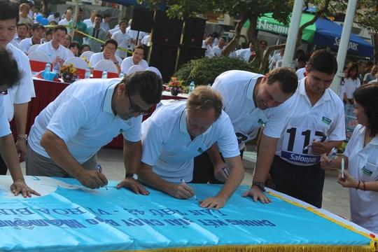 """Đại biểu, đại diện các công ty, đại sứ quán ký tên vào cờ hiệu """"Vì hòa bình"""" của giải chạy"""