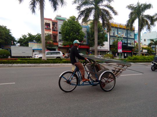 Xe xích lô chở ống thép chĩa ra phía người đi đường, rất nguy hiểm