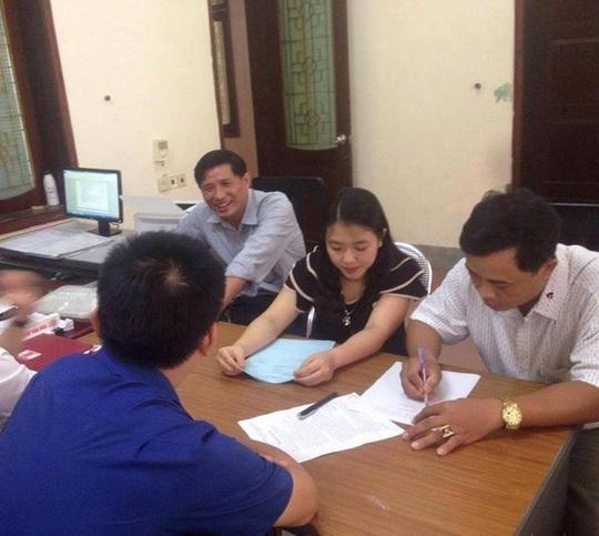 Ông Hoàng Khắc Sửu (người ngoài cùng bên phải) đang ký vào biên bản nhận tiền hỗ trợ.