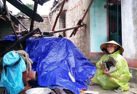 Bà Nguyễn Thị Hới (53 tuổi, ở thôn 12, xã Lộc Ninh) bủn rủn chân tay dọn dẹp lại đống đổ nát.