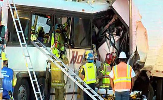 Các nhân viên cứu hộ phải dùng thang leo vào cửa sổ xe buýt để đưa thi thể nạn nhân ra ngoài. Ảnh: Reuters