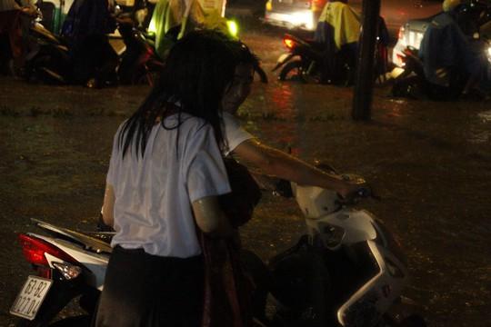 Hai em học sinh vất vả vượt qua dòng nước ngập trên đường Nguyễn Hữu Cảnh.