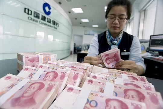 Kiểm tiền nhân dân tệ tại một ngân hàng của Trung Quốc Ảnh: REUTERS